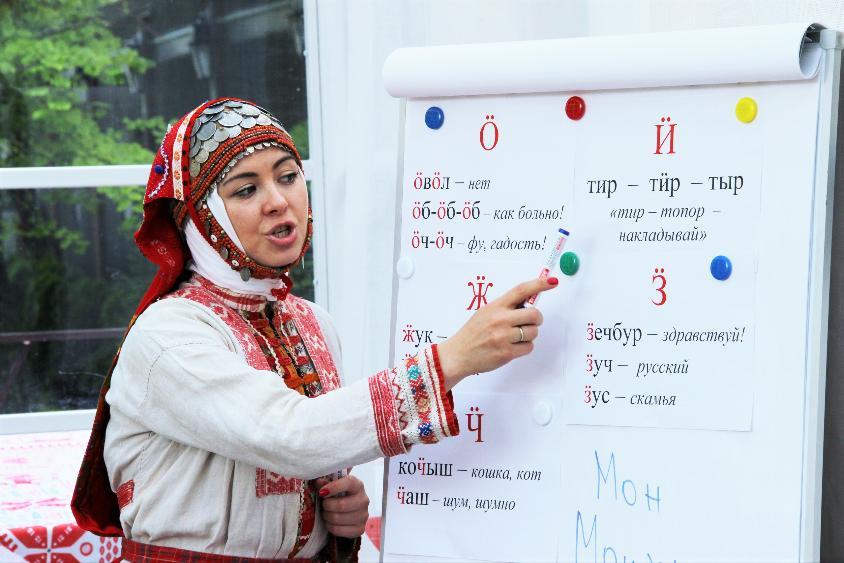 Фото девушка в удмуртском национальном костюме показывает слова на удмуртском на флипчарте