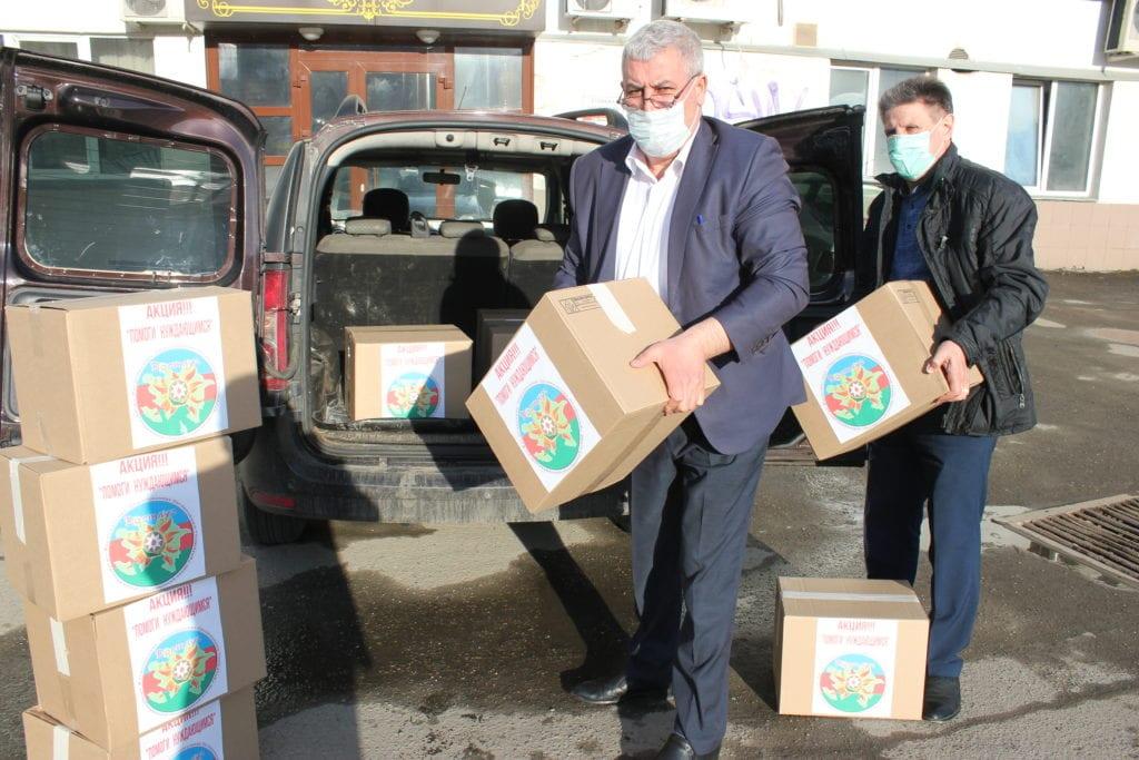 мужчины в масках разгружают машину с коробками благотворительной помощи по коронавирусу