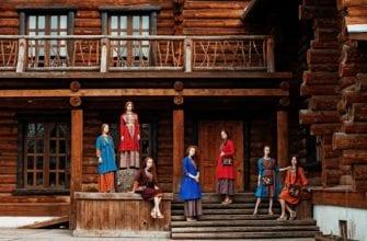 Девушки в этнических костюмах на фоне деревянного особняка