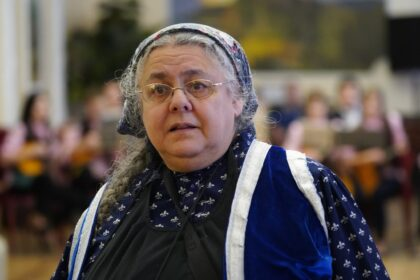 Фото Евы Тулуз, женщина в очках с длинной косой в косынке