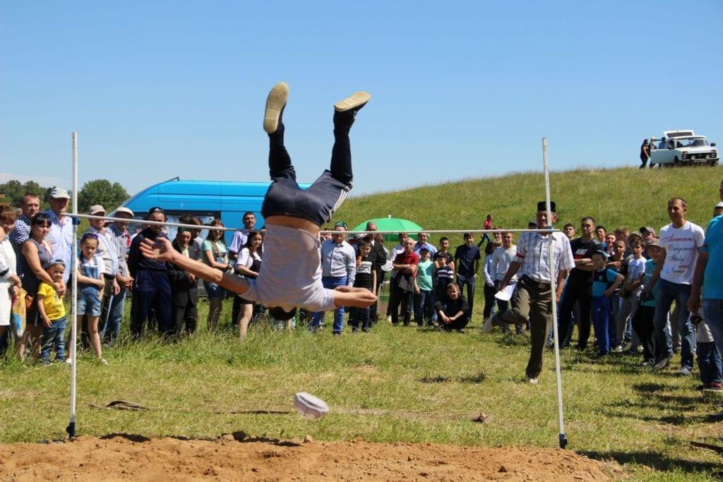 Фото с праздника Сабантуй, мужчина прыгает через перекладину, слетела шапка