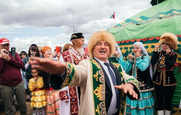 Фото мужчины, танцующего на празднике Сабантуй, на фоне девушек, играющих на варгане