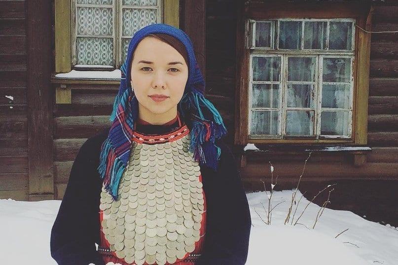 Фото удмуртской девушки в мостисто на фоне деревянного сельского дома