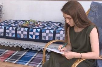 Фото с выставки Анны Образцовой в кресле-качалке, пишет карандашом в планшете