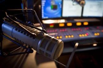Фото студийный микрофон на фоне звукового пульта и мониторов