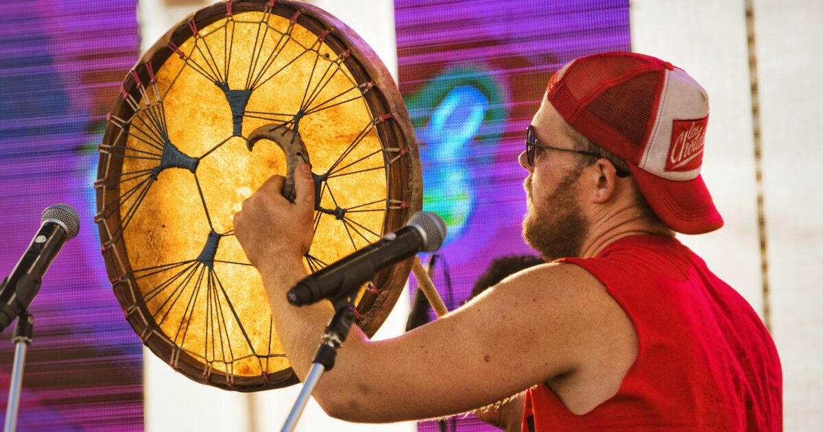 Фото фестиваль тангыра, музыкант группы У ЕН бьет в шаманский бубен