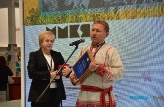Фото мужчины с дипломом у микрофона на московской книжной ярмарке