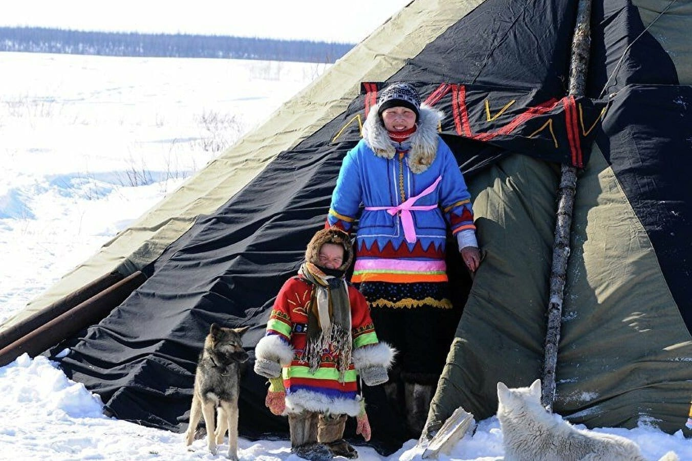 Фото два человека с собакой стоят возле юрты