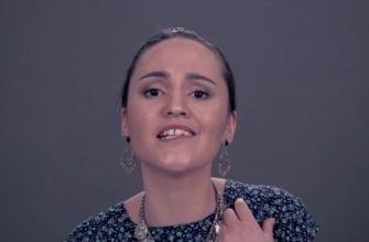 Фото лицо девушки с выразительным взглядом, большими серьгами на сером однородном фоне