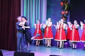 Фото девушки на сцене в красных платьях хлопают, мужчина обнимает женщину и дарит цветы