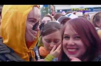 Фото девушка в оранжевом капюшоне и тёмных круглых очках, вторая девушка смеется