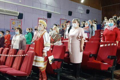 Фото зрители в зале в масках стоят и слушают гимн