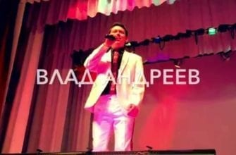 Фото Влад Андреев поет на сцене в белом костюме