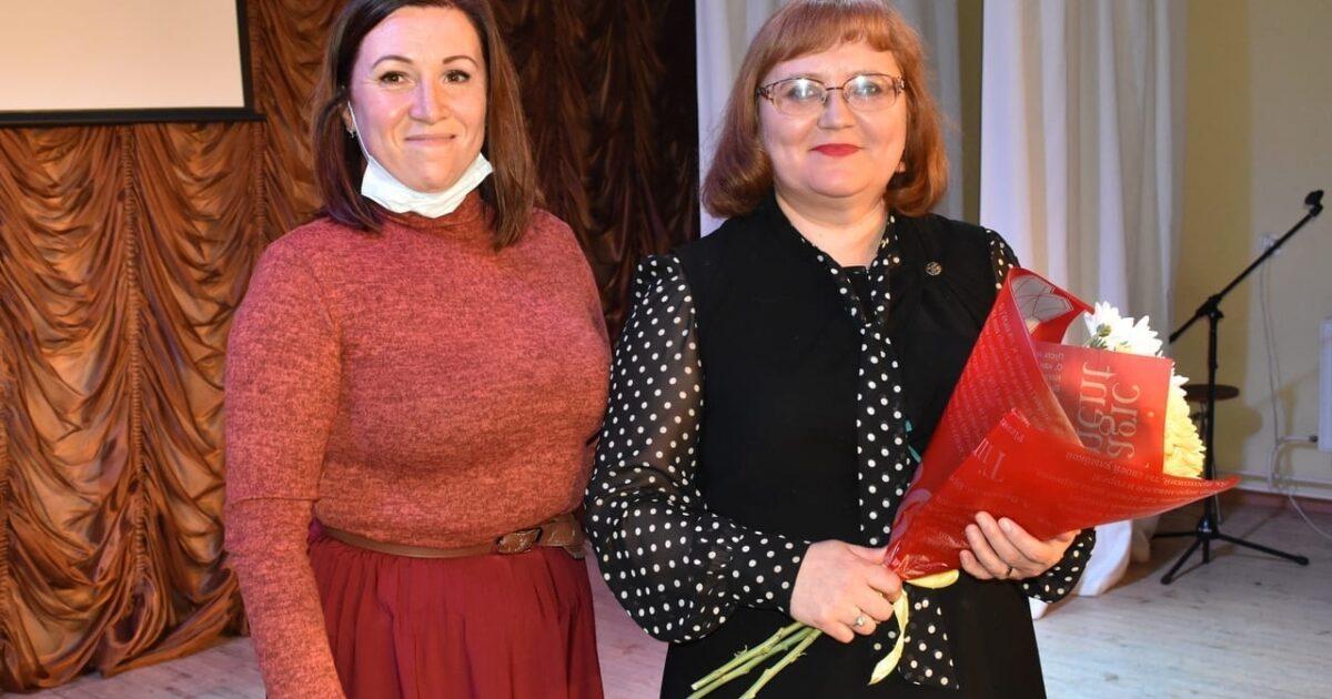 Фото две женщины на сцене, женщина в маске, опущенной до подбородка и женщина с белыми хризантемами в красной обертке