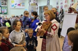 Фото женщина показывает детям книгу ручной работы со сказками