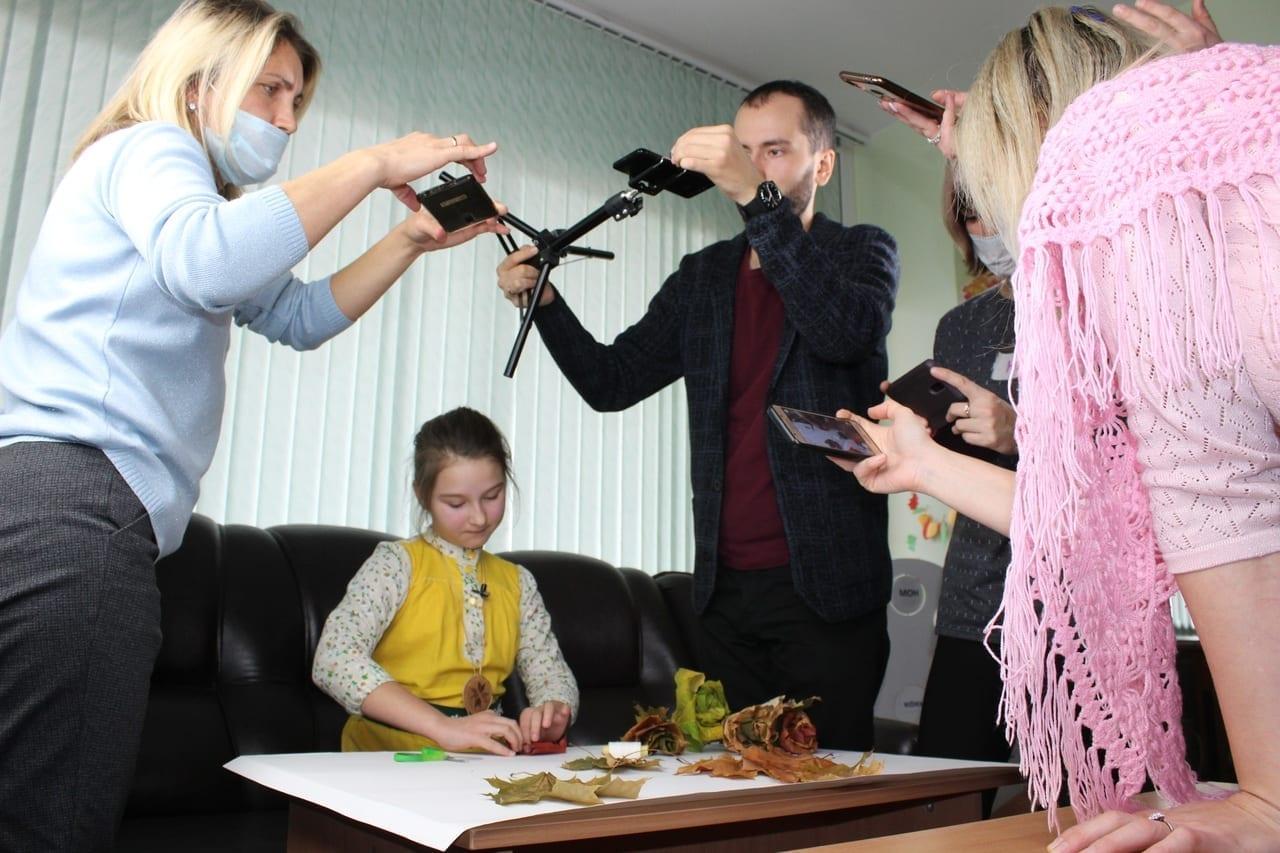 Фото девочка делает аппликацию из осенней листвы, а взрослые её снимают на телефон