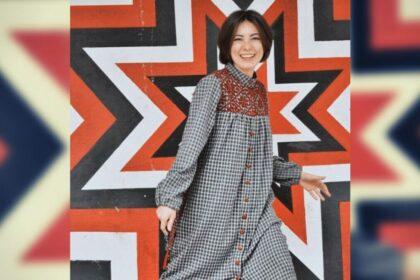 Фото девушки с орнаментом звезды толезё на платье, на фоне стены с красной восьмиконечной звездой