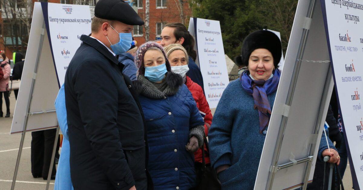 Фото мужчина и женщины рассматривают татарский стенд с татарскими словами