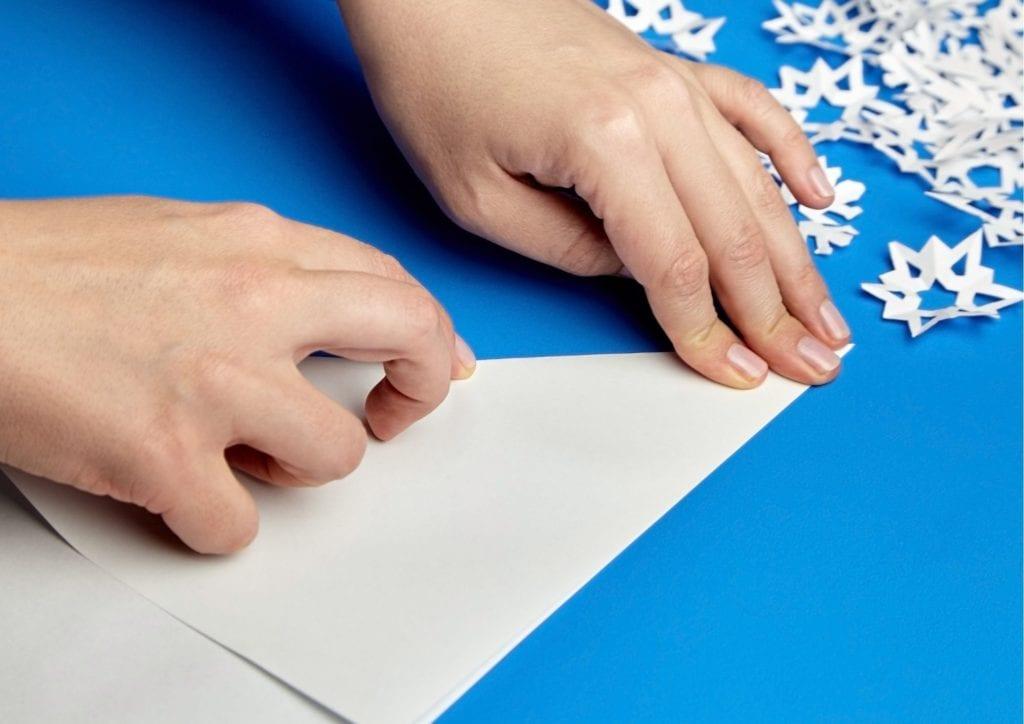 Фото руки сгибают и разглаживают макет снежинки