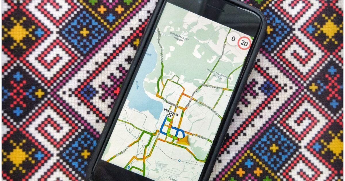 Фото смартфона с запущенным приложением яндекс навигатор на фоне разноцветного коврика